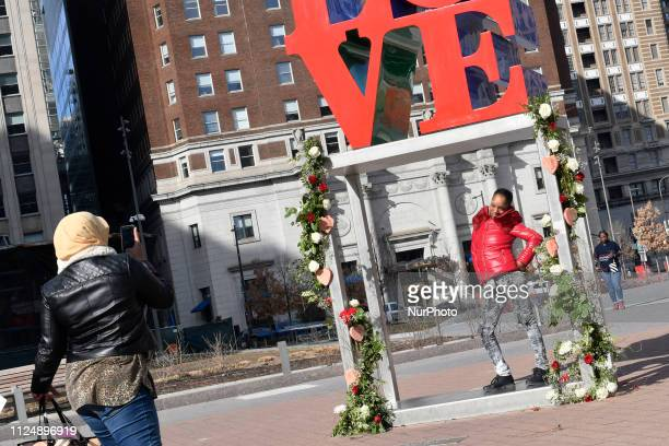 People are seen taking pictures for Instagram in front of a with bouquets of roses decorated LOVE Park statue in Philadelphia PA on Valentines Day...