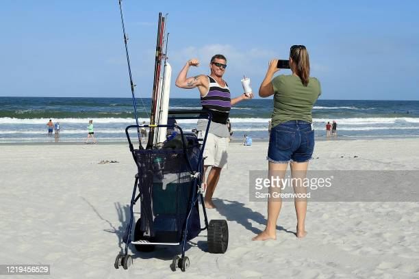 People are seen taking pictures on April 17 2020 in Jacksonville Beach Florida Jacksonville Mayor Lenny Curry announced Thursday that Duval County's...