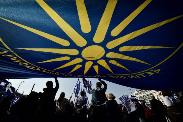 People Are Seen Under A Huge Flag Bearing A Giant Vergina Sun C