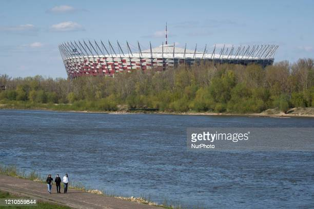 People are seen walking along the boulevard on the Vistula river with the National Stadium in the background in Warsaw, Poland on April 20, 2020. As...