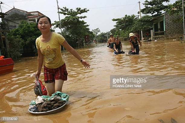 People are seen walking in a flooded street in Thach Thanh district in the central province of Thanh Hoa 08 October 2007 At least 58 people have died...