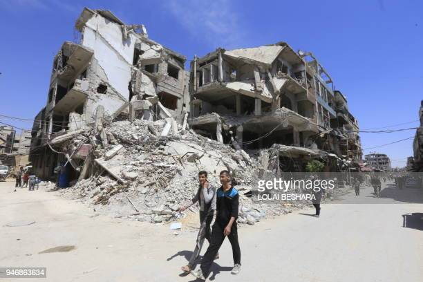 TOPSHOT People are seen walking in Douma on the outskirts of Damascus on April 16 2018 during an organised media tour after the Syrian army has...