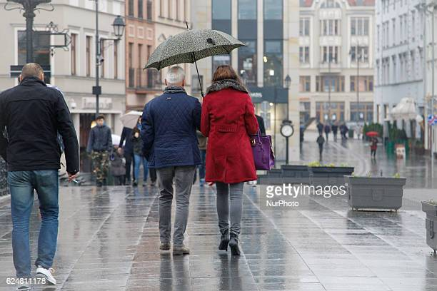 People are seen walking in the old centre of town on a rainy Saturday in Bydgoszcz Poland on November 19 2016