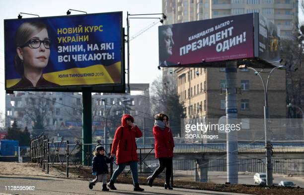 People are seen walking near political billboards of Ukrainian candidates of presidential election Yulia Tymoshenko leader of the Ukrainian political...