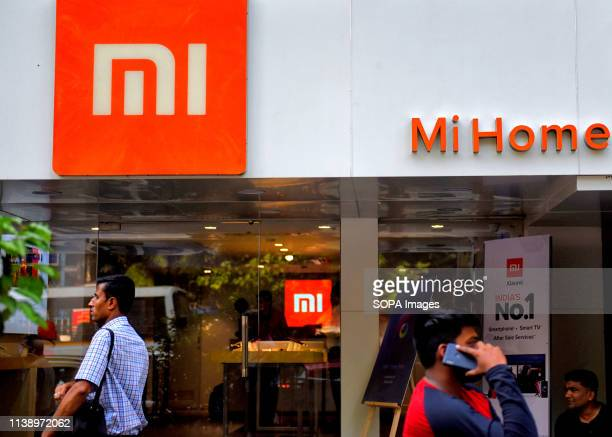 People are seen walking past an MI home mobile store in Kolkata.