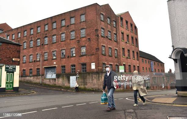 People are seen walking past an old mill with their shopping in the Market Town of Leek on November 11, 2020 in Leek, England. The United Kingdom...