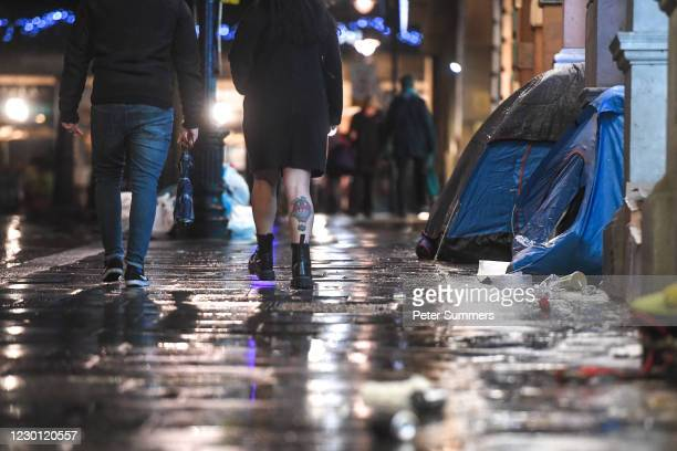 People are seen walking past homeless people's tents on December 13, 2020 in London, England. The number of new rough sleepers has risen in London...