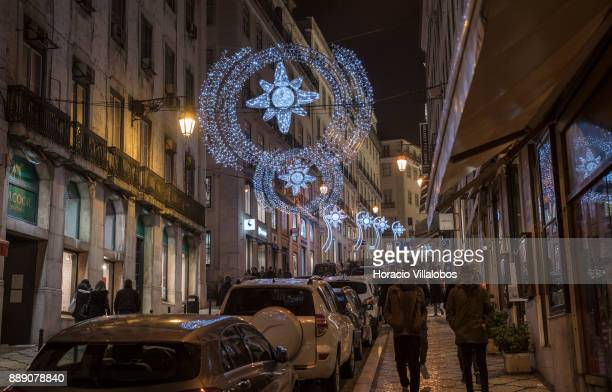 People are seen walking under Christmas and New Year light displays in Rua Nova do Almada on December 9 2017 in Lisbon Portugal The city shows a...