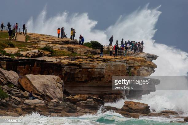 People are seen watching rough surf conditions at Ben Buckler point Bondi on May 22 2020 in Sydney Australia Winter weather including rain and strong...