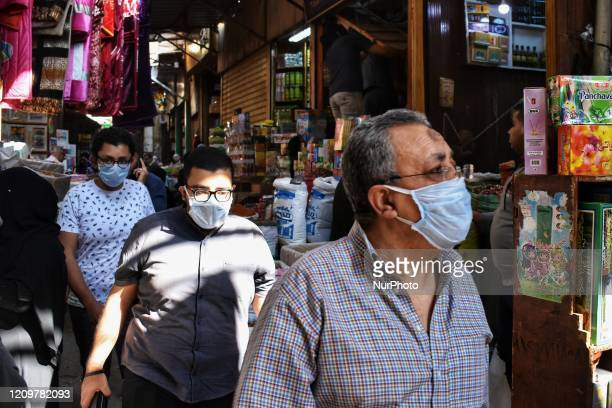 People are seen wearing a face mask at a street market for spices and herbs in Al Azhar district, Cairo, Egypt, 12 April 2020, where people usually...