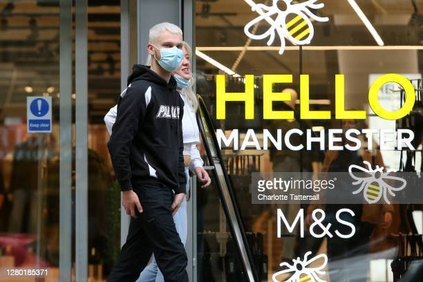 People are seen wearing face masks in Manchester City Centre on October 14, 2020 in Manchester, England. Under a new three-tier system, English...