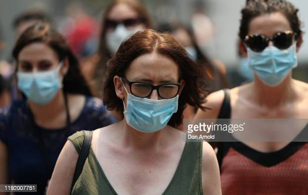 People are seen wearing face masks to protect from smoke haze as they cross a busy city street on December 05 2019 in Sydney Australia Smoke haze...
