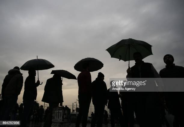 People are seen with their umbrellas during a rainfall at the Suleymaniye Mosque's courtyard in Istanbul Turkey on December 17 2017