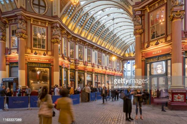 people are shopping in leadenhall market, london, united kingdom, early in the evening. - leadenhall market stock photos and pictures