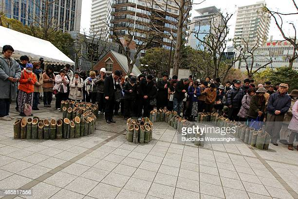 People are silent over the lighted bamboo candle that are placed in the shape of the date 311 to commemorate the victims of Great East Japan...
