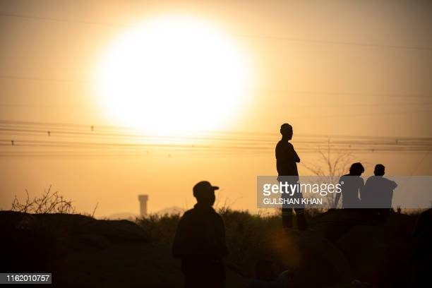 TOPSHOT People are silhouetted as they gather at Wonderkop in Marikana Rustenburg where striking miners were killed during the Marikana Massacre...