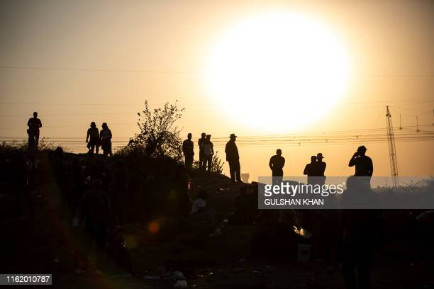 People are silhouetted as they gather at Wonderkop in Marikana Rustenburg where striking mineworkers were killed during the Marikana Massacre for the...