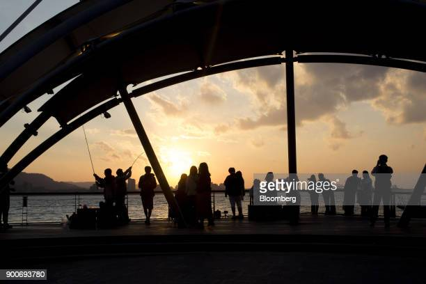 People are silhouetted as they gather near the water's edge at dusk in Taipei Taiwan on Wednesday Dec 27 2017 Taiwans currency rose 18 percent in...