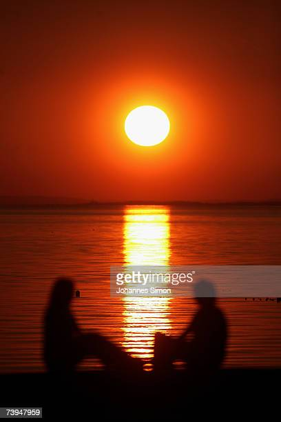 People are silhouetted at the beach of Lake Constance during sunset on April 22 in Langenargen Germany According to weather forcasts the unusual warm...
