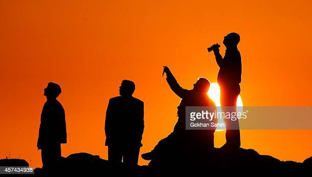 People are silhouetted on the top of a hill close to the border line between Turkey and Syria near Mursitpinar bordergate as they watch the US led...