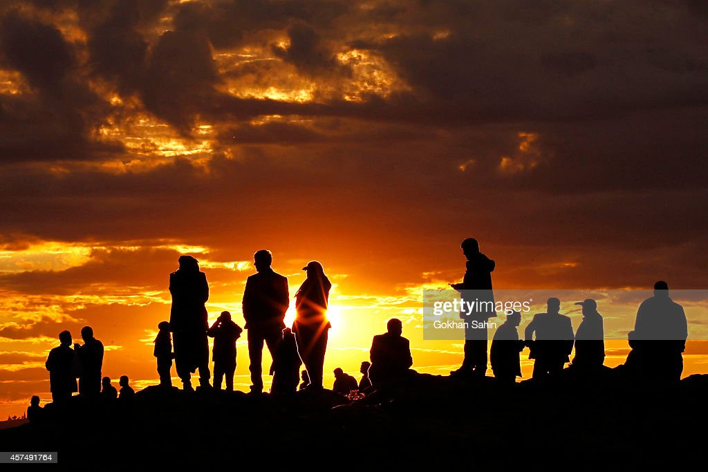 People are silhouetted on the top of a hill close to the border line between Turkey and Syria near Mursitpinar bordergate as they watch the U.S led airstrikes over ther Syrian town of Kobani on October 19, 2014. Kurdish fighters in Syrian city of Kobani have pushed back Islamic State militants in a number of locations as U.S. air strikes on ISIS positions continue in and around the city. In the past month more than 200,000 people from Kobani have fled into Turkey.