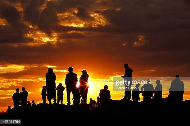 People are silhouetted on the top of a hill close to the border line between Turkey and Syria near Mursitpinar bordergate as they watch the U.S led...