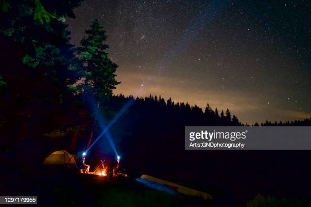 people are sitting next to the campfire at the campsite while they are lighting the sky with a forehead  lanterns - uncultivated stock pictures, royalty-free photos & images