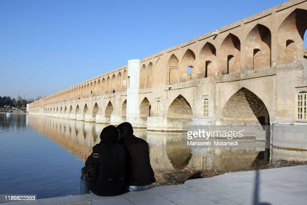 people are sitting next to the si o seh pol  bridge in isfahan, iran - ザーヤンド川 ストックフォトと画像