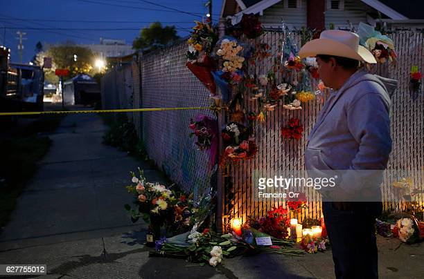 People are stopping by and dropping off flowers and candles near the site of the warehouse fire in Oakland CA December 4 2016 A fire broke out during...