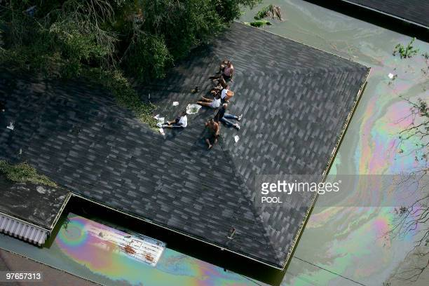 People are stranded on a roof due to flood waters from Hurricane Katrina 30 August 2005 in New Orleans, Louisiana. It is estimated that 80 percent of...