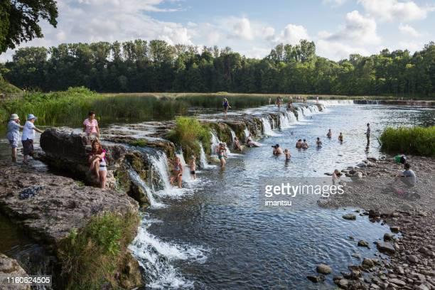 la gente está nadando en la cascada ventas rumba, kuldiga, letonia - letonia fotografías e imágenes de stock