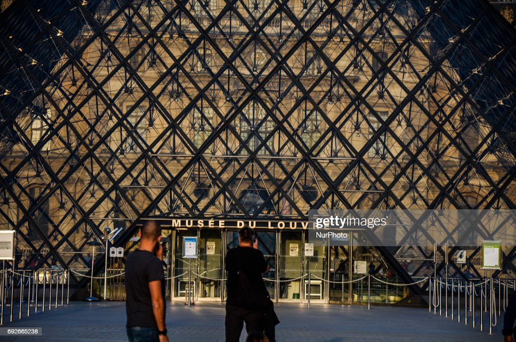 People are taking pictures in front of Louvre museum in Paris. People used the first days of the summer for walking around the French capital of Paris. The temperature of the weather is about 25 celsius degrees Paris, France on June 04, 2017