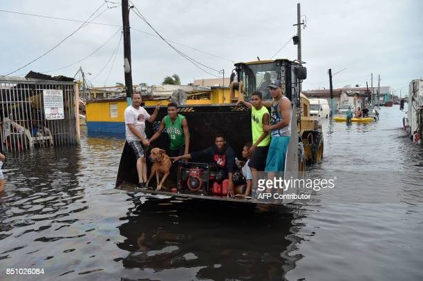People are transported down a road flooded by Hurricane Maria is seen in Juana Matos Catano Puerto Rico on September 21 2017 Puerto Rico braced for...