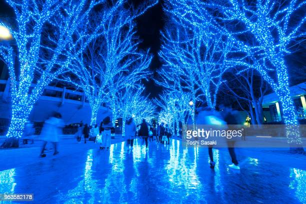 People are walking down and taking photos in the Blue Cave (Ao No Dokutsu) Keyaki Namiki (Zelkova tree–lined), which are illuminated by million of blue LED lights at Yoyogi Park Shibuya Tokyo Japan on 11 December 2017. Blue LED reflects to the path.
