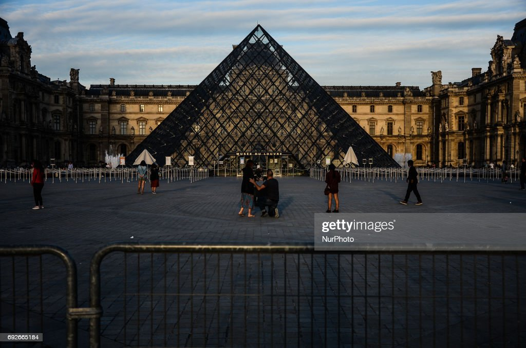 People are walking in front of the Louvre museum in Paris. People used the first days of the summer for walking around the French capital of Paris. The temperature of the weather is about 25 celsius degrees Paris, France on June 04, 2017
