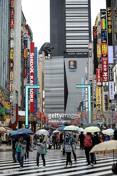 People are walking on the street while a 12 meters tall Godzilla replica based on the original 1954 film is seen on the top of the ninefloor Toho...