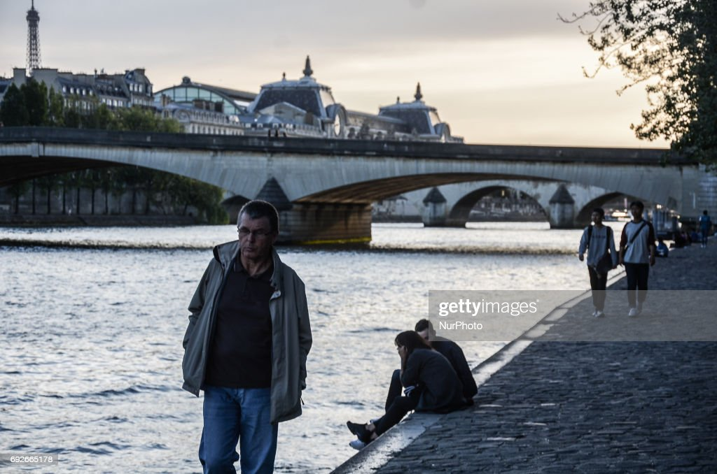 People are walking past the Seine river in Paris. People used the first days of the summer for walking around the French capital of Paris. The temperature of the weather is about 25 celsius degrees Paris, France on June 04, 2017