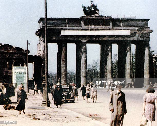 People are walking through Brandenburg Gate from both directions July 1945 A car is parked next to the sidewalk A 5 km speed limit is posted near the...