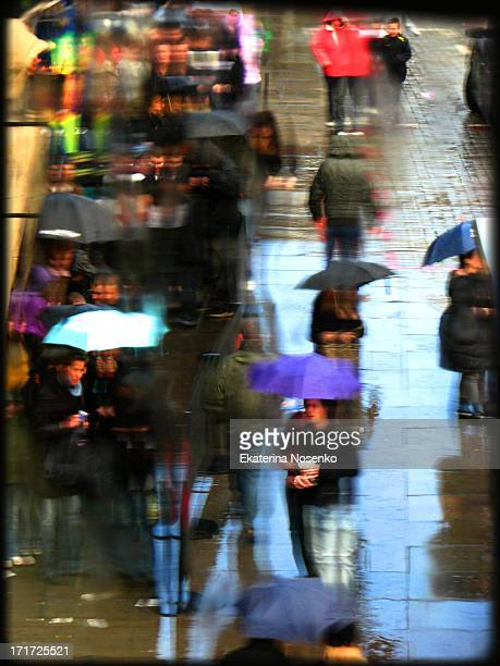 People are walking under colourful umbrellas on a rainy day in London.