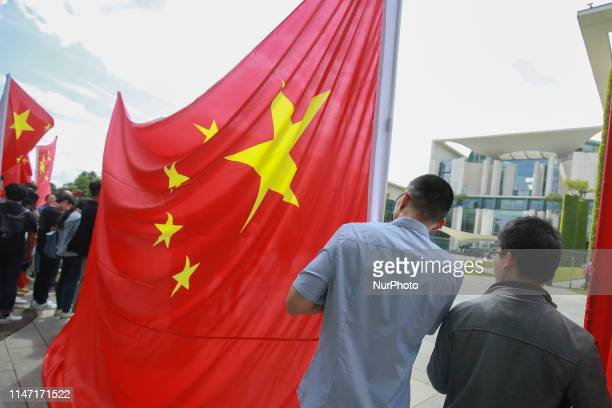 People are waving a big Chinese flag during the visit of Vice President of the People's Republic of ChinaWang Qishan outside the Chancellery on May...