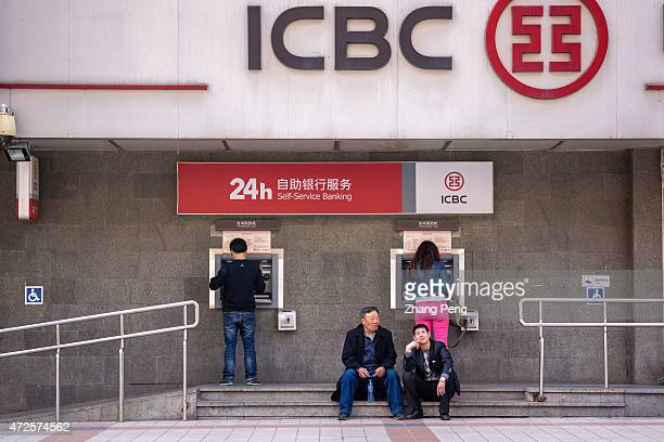 People are withdrawing money from the ATM of an ICBC branch on Beijing Wangfujing commercial street Industrial Commercial Bank of China Ltd reported...