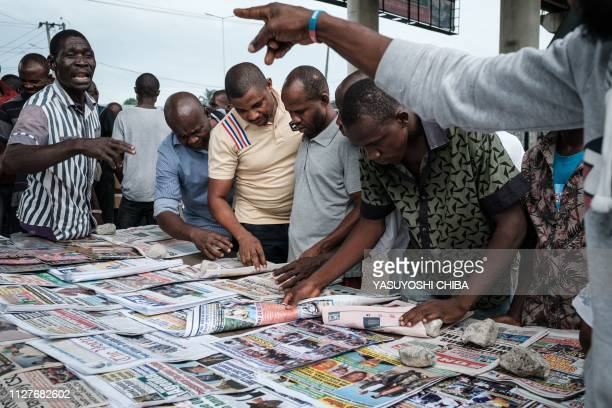 People argue over the result of Nigeria's Presidential election results at a newspaper stand in Port Harcourt Southern Nigeria on February 27 2019...