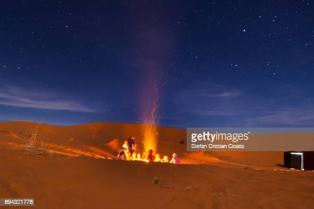 people around a desert fire camp in sahara - merzouga stock pictures, royalty-free photos & images