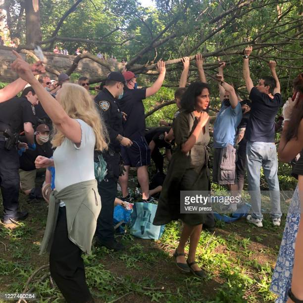 "People around help the Police ""nto rescue three people who get injured after a branch falls on them in Riverside Community Park in Upper West Side..."
