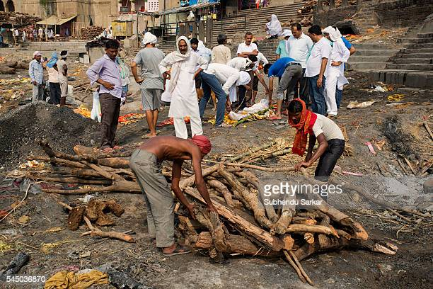 People arrange logs of wood to cremate a corpse at Manikarnika ghat in Varanasi. It is a traditional holy place on the banks of river Ganges to...