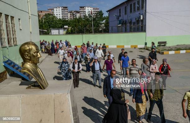 People arrive at a polling station to vote in snap twin Turkish presidential and parliamentary elections in the Kurdish stronghold of Diyarbakir in...