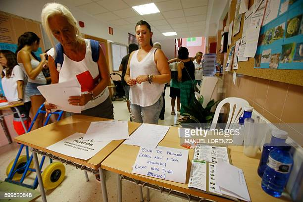 People arrive at a Red Cross center after evacuating their homes due to forest fires along the coastline in the Spanish resort of Javea Valencia...