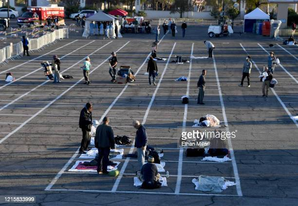 People arrive at a temporary homeless shelter with socialdistancing boxes set up in a parking lot at Cashman Center on March 30 2020 in Las Vegas...