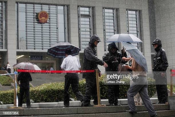People arrive at Anhui provincial court as China opens the murder trial of Gu Kailai, the wife of disgraced Chinese politician Bo Xilai, in on August...