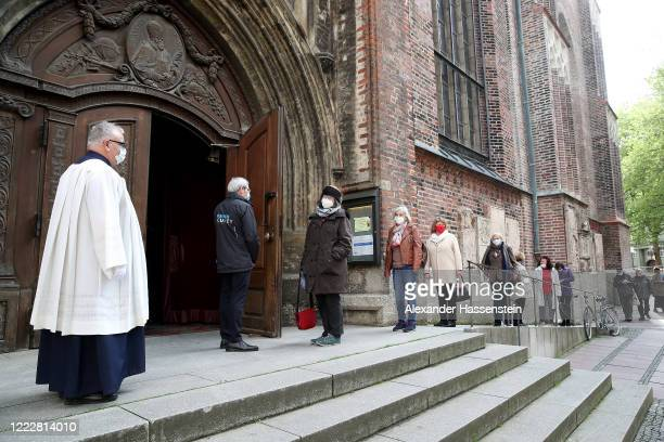 People arrive at Frauenkirche 'Cathedral of Our Lady' cathedral for evening holy mass on the first day churches and other houses of worship are...